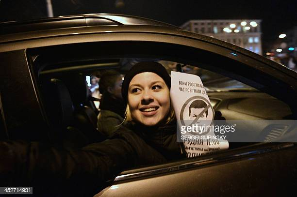 A woman holds a sign bearing a portrait ofUkrainian President Viktor Yanukovych and reading 'traitor' as she sits in a car during a rally on...