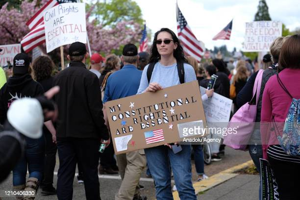 A woman holds a sign calling constitutional rights essential as hundreds of protesters demonstrate outside the state Capitol to speak out against...