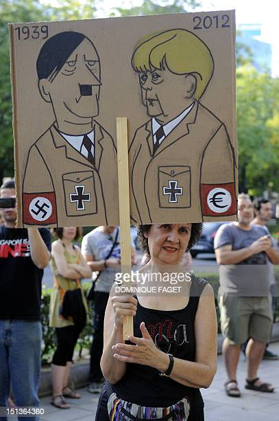 A woman holds a sign comparing Adolph Hitler to German Chancellor Angela Merkel during a demonstration against her official visit to Spain in central...