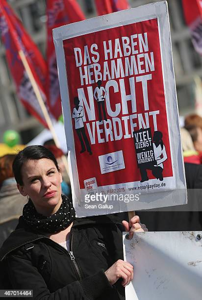 A woman holds a sign demanding better work conditions for midwives at a rally for equal pay for women compared to men on Equal Pay Day in front of...