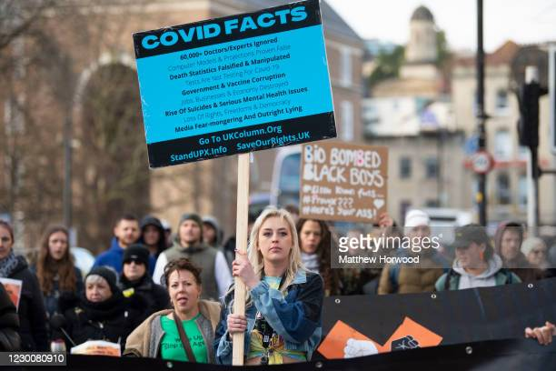 Woman holds a sign displaying COVID facts during an anti-vaccine protest which started at College Green on December 12, 2020 in Bristol, England. NHS...
