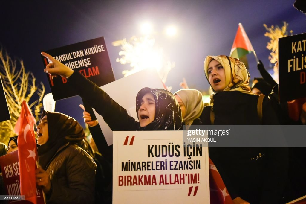 A woman holds a sign during a demonstration against the US and Israel at Fatih Mosque in Istanbul on December 6, 2017. Hundreds of people staged protests in Istanbul angrily denouncing the US president's move to recognise Jerusalem as the capital of Israel. /