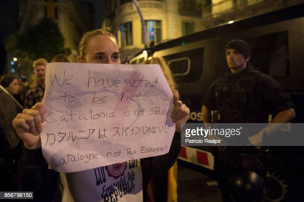 A woman holds a sign during a protest against the violence that marred yesterdays referendum vote outside the General Direction of the National...