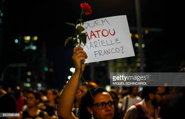TOPSHOT A woman holds a sign during a rally against the murder of Brazilian councilwoman and activist Marielle Franco in Sao Paulo Brazil on March 15...
