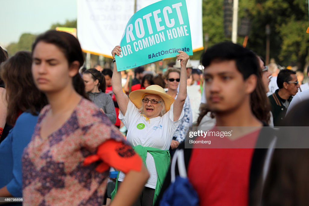 A woman holds a sign during the Moral Action on Climate Justice rally on the National Mall in Washington, D.C., U.S., on Thursday, Sept. 24, 2015. 'Climate change is a problem which can no longer be left to a future generation, Pope Francis said at the White House yesterday. Photographer: Oliver Contreras/Bloomberg via Getty Images