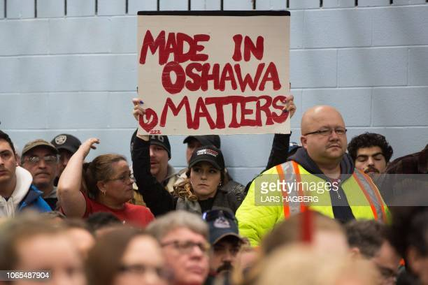 A woman holds a sign during the press conference with union leaders at Local 222 in Oshawa Ontario on November 26 2018 In a massive restructuring US...