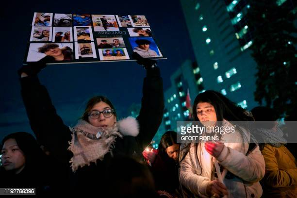 TOPSHOT A woman holds a sign for one of the victims of Ukrainian Airlines flight 752 which crashed in Iran during a vigil at Mel Lastman Square in...