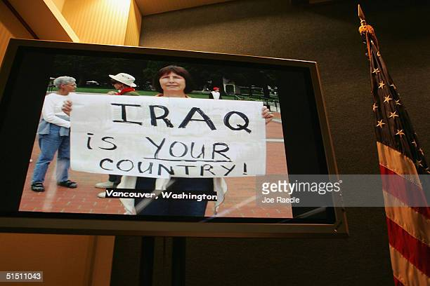 A woman holds a sign in a picture she submitted to The Fellowship of Reconciliation Iraq Photo Project during a running video slide show at a news...