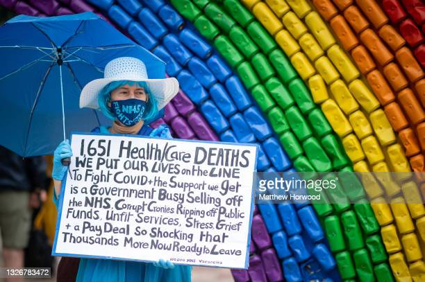 Woman holds a sign in front of a rainbow flag during a protest on July 3, 2021 in Cardiff, United Kingdom. On July 05, 1948 the National Health...