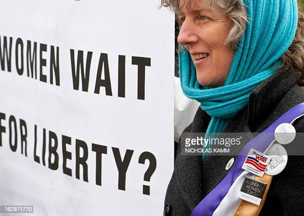 Woman holds a sign in front of the White House in Washington on March 2, 2013 during an event to commemorate the 100th anniversary of the Suffrage...