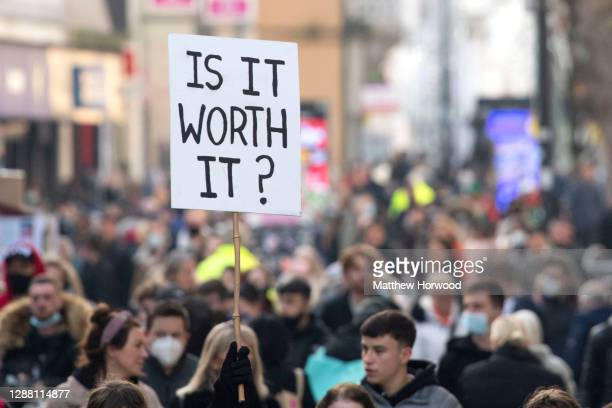A woman holds a sign in the air saying is it worth it on a busy Queen Street on Black Friday on November 27 2020 in Cardiff Wales Restrictions across...