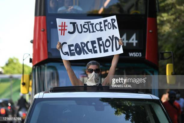 Woman holds a sign out of the sunroof of a car in central London on May 31, 2020 calling for justice following the death of George Floyd, an unarmed...