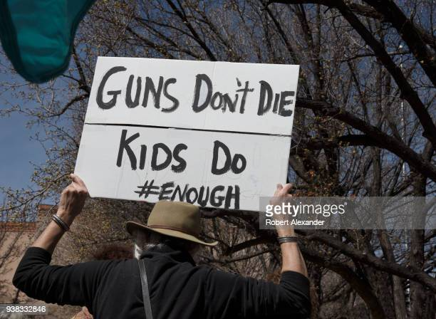 A woman holds a sign over her head referring to school shootings during a 'March For Our Lives' rally in Santa Fe New Mexico The rally and march part...