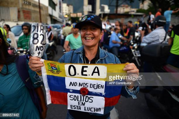 A woman holds a sign reading Day 82 No more and a Venezuelan national flag reading OAS don't leave us alone in the fight during a march towards the...