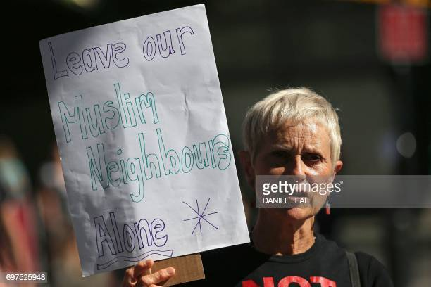 A woman holds a sign reading 'Leave our Muslim Neighbours Alone' as she stands near the scene in Finsbury Park area of north London after a vehicle...