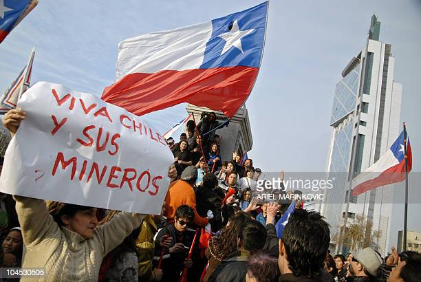 A woman holds a sign reading 'Long live Chile and its miners' as Chileans celebrate in the streets of Santiago after the confirmation of the survival...