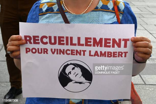 """Woman holds a sign reading """"meditation for Vincent Lambert"""", who is in a vegetative state since 2008, during a vigile in front of the Saint-Sulpice..."""