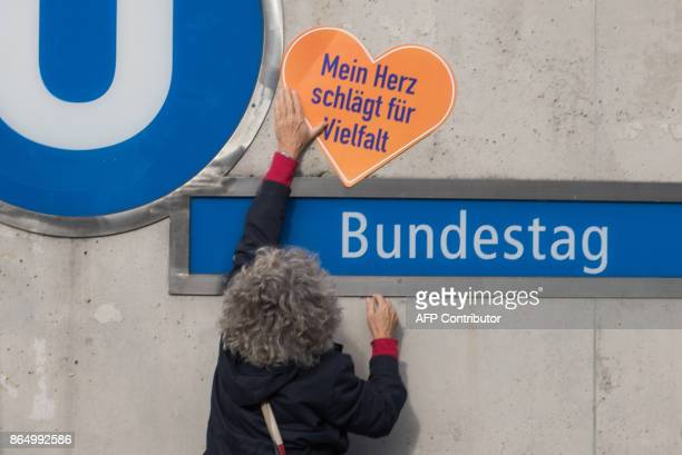 A woman holds a sign reading My heart beats for diversity at the subway station Bundestag during a demonstration against hate and racism in the...