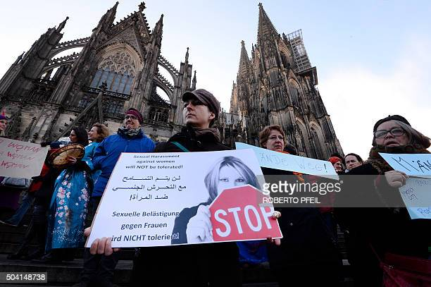 A woman holds a sign reading 'Sexual harassment against women will not be tolerated' while taking part in a demonstration in front of the cathedral...