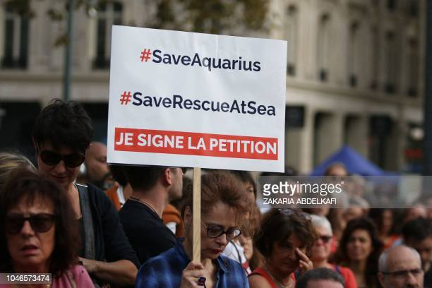 A woman holds a sign reading 'sign the petition' during a demonstration in support to the Aquarius an NGO boat dedicated to the rescue of migrants at...