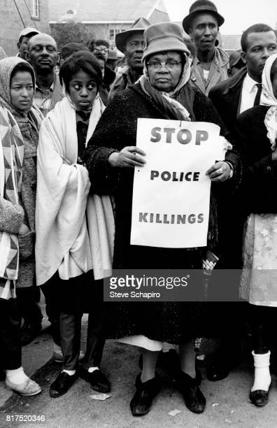 Woman holds a sign reading: 'Stop Police Killings', during the Selma to Montgomery march, Alabama, March 1965.