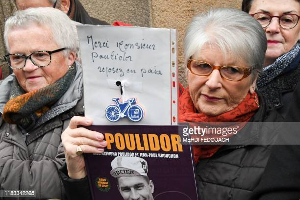 TOPSHOT A woman holds a sign reading Thank you to mister Poulidor rest in peace as people attend the funerals of French cyclist Raymond Poulidor in...