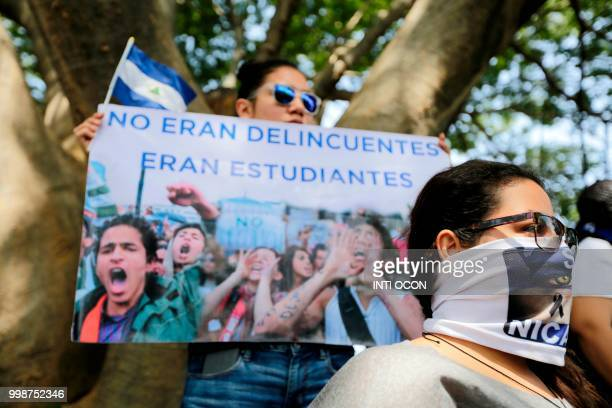 A woman holds a sign reading They were not criminals they were students as people wait for the arrival of the students of the National Autonomous...
