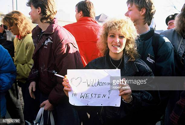 Woman holds a sign reading Welcome to the West for East Germans as they enter West Berlin after the opening of the Berlin Wall.