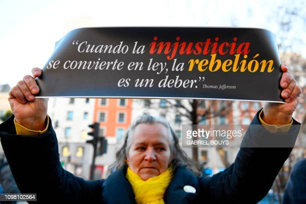 A woman holds a sign reading When injustice becomes law rebellion is a must during a protest against the trial of jailed Catalan separatists at the...