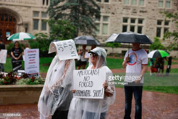 Woman holds a sign saying Americans! No forced experimental shots during the demonstration. Anti-vaxxers and anti-maskers gathered at Indiana...