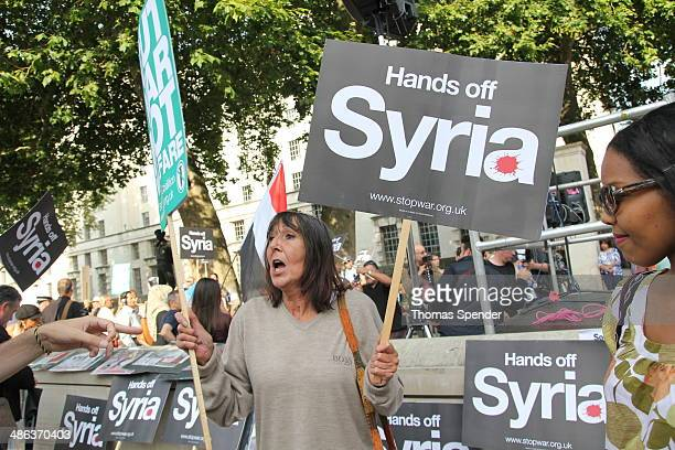 Woman holds a sign saying 'Hands off Syria' at a demonstration opposite Downing Street in London at a time when the UK appeared ready to join a US...