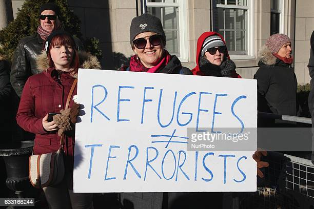 Woman holds a sign saying 'refugees do not equal terrorists' during a massive protest against President Trump's travel ban outside of the US...