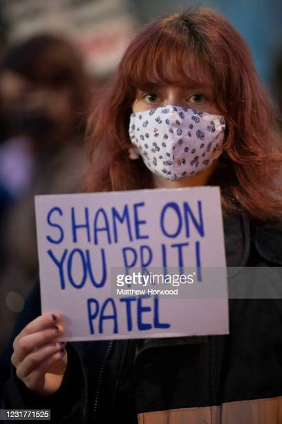 Woman holds a sign saying 'Shame on you Priti Patel' during a protest outside Cardiff Central Police Station on March 17, 2021 in Cardiff, Wales....