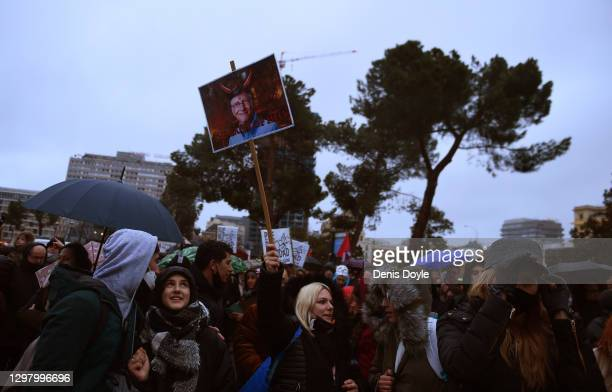 Woman holds a sign showing a doctored image of Bill Gates wearing horns during a demonstration against Covid-19 restrictions on January 23, 2021 in...