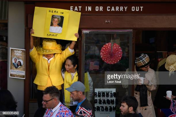 A woman holds a sign showing Princess Diana and the message Here In Spirit on the route of the procession as media tourists and royal fans gather...