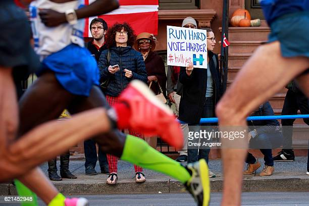 A woman holds a sign supporting both runners and Democratic presidential candidate Hillary Clinton as runners pass by on Lafayette Avenue during the...