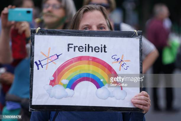 A woman holds a sign that reads Freedom and refers to vaccines and Bill Gates at a gathering of coronavirus skeptics in front of the Brandenburg Gate...