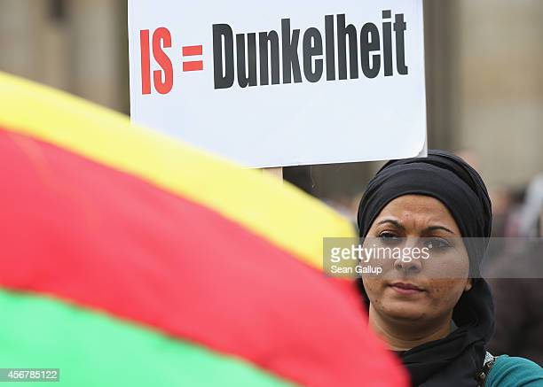 A woman holds a sign that reads IS=Darkness at a rally by expatriateKurds who were protesting against the ongoing violence by militias of the Islamic...