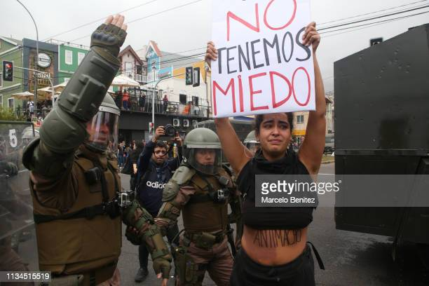 A woman holds a sign that reads 'We are not afraid' next to police officers during a demonstration as part of the International Women's Day on March...