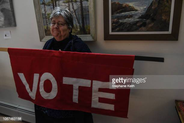 """Woman holds a sign that says """"vote"""" at a campaign event with Democratic Gubernatorial candidate Christine Hallquist on November 4, 2018 in..."""