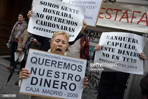 A woman holds a sign which reads 'we want our money' as she protests against Rodrigo Rato former chairman of Spanish bank Bankia as he enters...