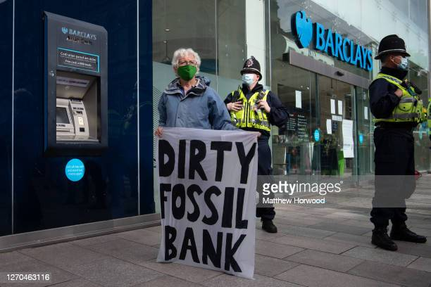 "A woman holds a sign which says ""dirty fossil bank"" in front of Barclays Bank on the Hayes in Cardiff on September 3 2020 in Cardiff Wales Extinction..."