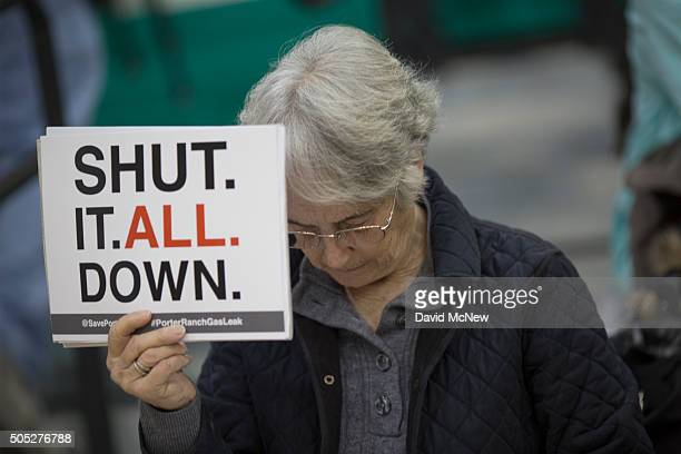 A woman holds a sign while attending a public hearing before the South Coast Air Quality Management District regarding a proposed stipulated...