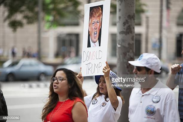 A woman holds a sign while marching to Trump Hotel during a protest against Donald Trump candidate for the Republican Presidential ticket after he...