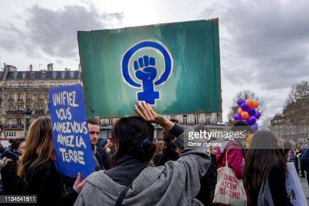 A woman holds a sign with a feminist symbol during the International Women's Rights Day protest on March 08 2019 in Paris France Several thousand...