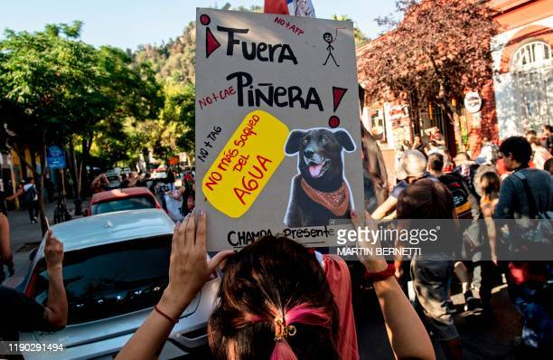 A woman holds a sign with an image of the socalled Negro Matapacos dog during a protest in Santiago on December 20 2019 The social movement that...