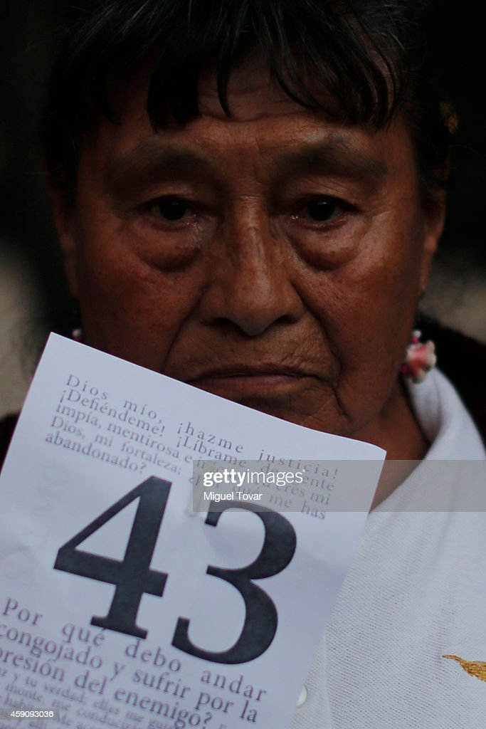A woman holds a sign with the number of the 43 missing students of Ayotzinapa during a demonstration against Mexico's government who suggests that 43 missing students were murdered and their charred remains tipped in a rubbish dump and a river in Guerrero, Mexico, on November 16, 2014 in Mexico City, Mexico.