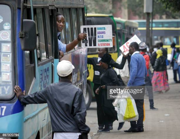 A woman holds a signboard with information according the destination out of the window of a bus before its departure Street scene in Nairobi capital...