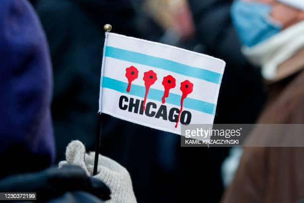 Woman holds a small flag depicting bullet holes with blood during an anti gun violence march on the Magnificent Mile in Chicago, Illinois, on...