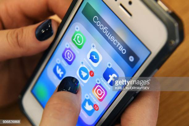 A woman holds a smart phone with the icons for the social networking apps Facebook Instagram Twitter and others seen on the screen in Moscow on March...